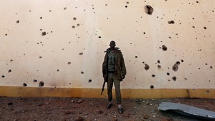 A Malian solider stands near a wall with bullet holes in the recently liberated town of Konna.