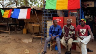 Men sit outside a shop as Malian and French flags decorate the area in Sevare, near Gao.