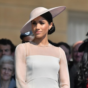 Meghan was elegant in a cream dress and hat.
