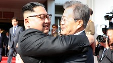 North and South Korea leaders share a surprise embrace