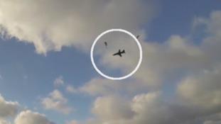 Jet flies through paragliders