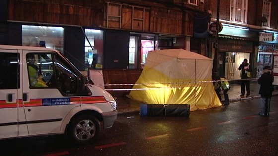 Police remain on the scene in Camden, north London where a man was killed after a sign fell from a store