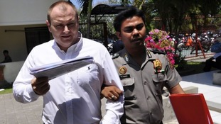 Paul Beales escorted by a policeman as he arrived for a court appearance