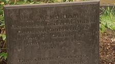A gravestone in the park.
