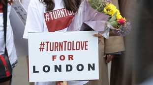 A group called Turn To Love held placards bearing slogans of hope near the bridge.
