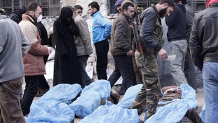 A woman is seen crying as relatives attempt to identify bodies found dead with their hands bound in Aleppo