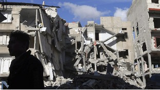 A Free Syrian Army fighter stands in front of a building destroyed by a Syrian Air force air strike in Damascus