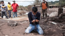 A man cries as rescue workers survey the damage from the volcanic eruption