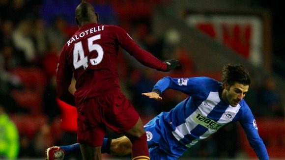 Balotelli tackles Wigan Athletic's Jordi Gomez