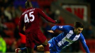 Balotelli tackles Wigan Athletic's Jordi Gomez