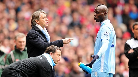 Balotelli (right) receives advice from manager Roberto Mancini