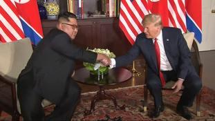 Donald Trump and Kim Jong Un shake hands ahead of their meeting