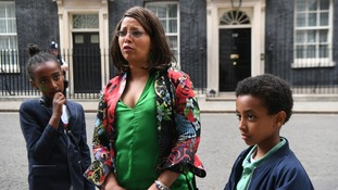 Local resident Judith Zacharias (centre) with her children Soliana and Alexander outside 10 Downing Street in London.