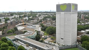 Grenfell Tower is now covered in white sheeting a green heart.