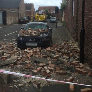 The parked car was badly damaged as bricks crashed on to the road