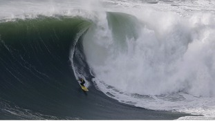 Big-wave surfer Garrett McNamara drops in on a large wave at Praia do Norte in Nazare