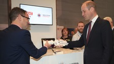 The Duke of Cambridge shakes hands with a robotic hand made by a 3D printer