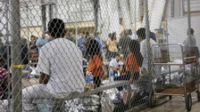 Those who have entered the United States illegally sit in a holding facility.