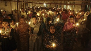 Pakistani Christians hold candles during an Easter vigil Mass in a church in Lahore on Saturday