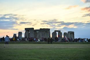 Crowds gather to watch the sun rise behind the Heel Stone.