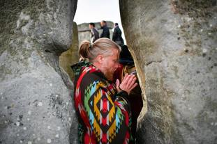 A man prays at Stonehenge.
