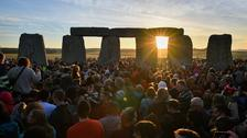 The sun shines through the stones at Stonehenge.