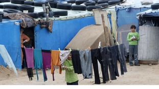 A Syrian child looks through clothing hanging on a line at a refugee camp
