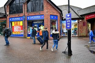 Shoppers walk past the police cordon in the Maltings area