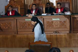 Aman Abdurrahman reacts after his sentence hearing at South Jakarta District Court