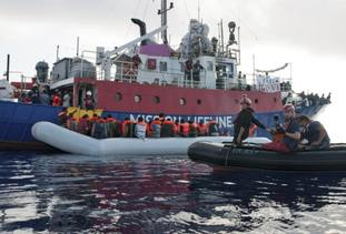 The ship operated by Mission Lifeline rescues migrants from a rubber boat in the Mediterranean Sea