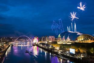 Drones fly in formation to make a letter N with fireworks above the River Tyne