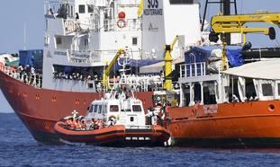 An Italian Coast Guard boat approaches the French NGO SOS Mediterranee Aquarius ship