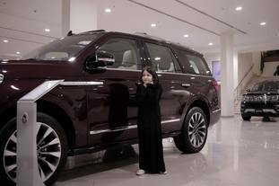 A child stands next to a car at a showroom in Riyadh