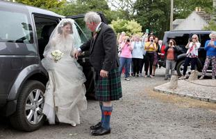Rose Leslie is helped out of her wedding car by her father