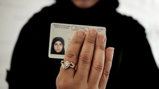 A woman holds her new driving licence.