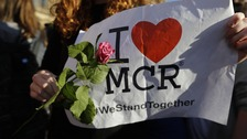 Someone holds an I Love Manchester poster and a rose