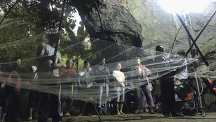 A group of locals and relatives perform a ritual calling for those who are missing at the entrance of the cave.