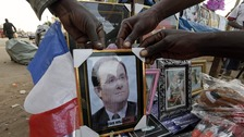 Malians display a picture of French President Francois Hollande for sale in Bamako market