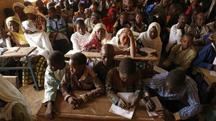 Children listen to a school teacher after the reopening of Mahamane Fondogoumo school in the centre of Timbuktu