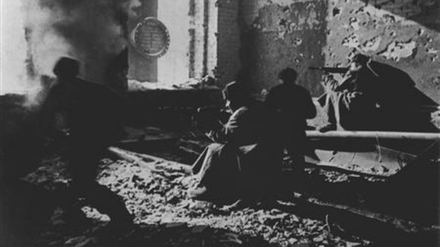 Red Army soldiers fire from a ruined building as they fight against Nazi troops.