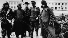 Captured Nazi servicemen stand in front of a damaged building in the city of Stalingrad (now Volgograd) in December 1943.