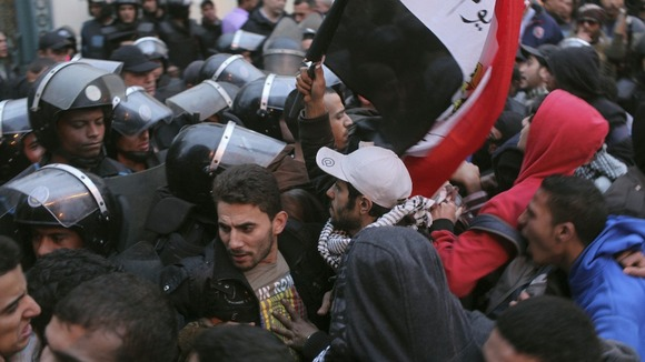 Police and protesters scuffle as protesters try to break through a gate of the presidential palace during protests in Cairo.
