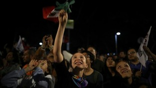 A supporter of presidential candidate Andres Manuel Lopez Obrador waves a Mexican flag.