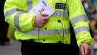 A policeman distributes witness appeal leaflet
