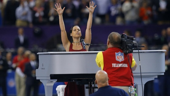 Singer Alicia Keys acknowledges the crowd while performing America's National Anthem before the start of the game.