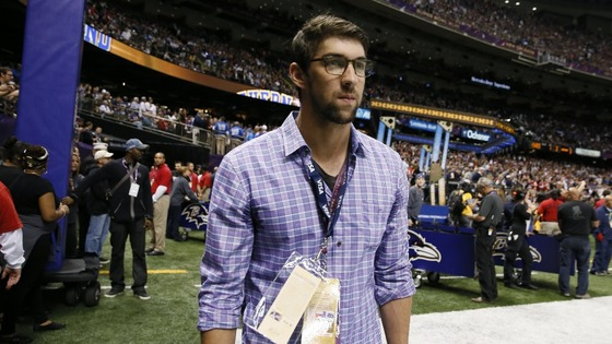 Former Olympic swimmer Michael Phelps watches from the sidelines.