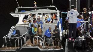 Rescued tourists from a boat that sank are helped on to a pier on the island of Phuket.
