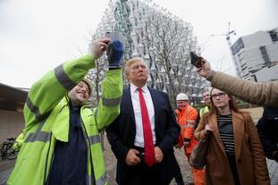 People take selfies with the Madame Tussauds wax figure of the president outside the new US Embassy in Nine Elms.