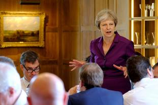 Theresa May at the Chequers meeting where Boris Johnson compared defending the plan to 'polishing a turd' but backed it along with his colleagues