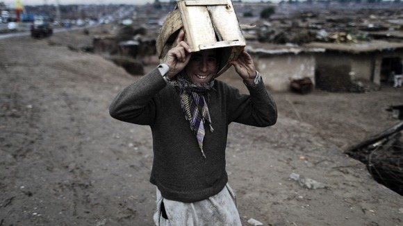 A boy uses a crate to take shelter from the rain